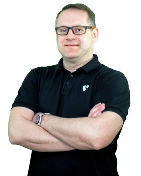 Jürgen Tomek mit Brille, schwarzem Polo-Shirt, Hände verschränkt